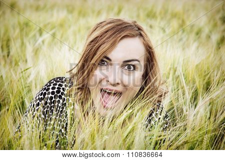 Young Woman Makes Crazy Face In Wheat Field By Sunset
