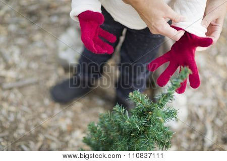 Caring Mother Putting Red Mittens On Child Near Small Christmas Tree Abstract.