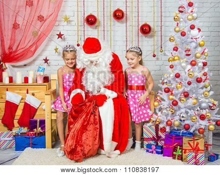 Santa Claus Pulls Out A Bag Of Gifts To Two Girls