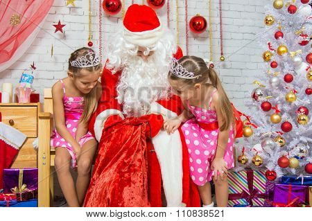 The Girls Look In The Bag Of Santa Claus