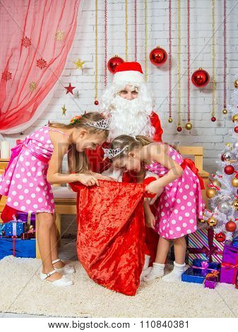 The Girls Digging In The Bag With Gifts That Brought Santa Claus