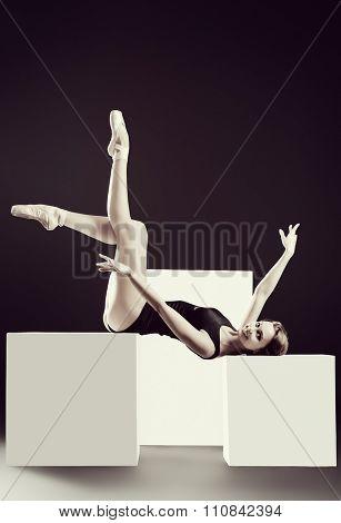 Elegant beautiful ballet dancer in black ballet leotard posing at studio on white cubes. Art concept.