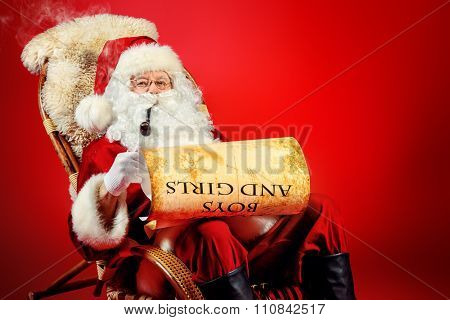 Santa Claus reading the list of presents and smoking a pipe in a rocking chair over red background. Christmas.