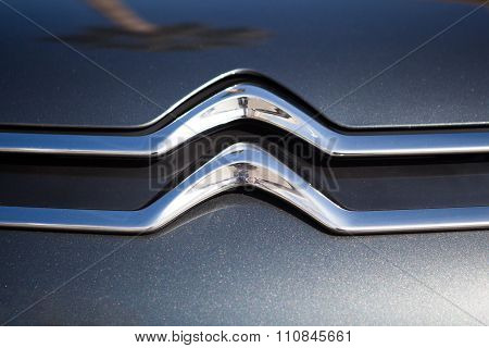 MALAGA, SPAIN - DECEMBER 2, 2015: Citroen car front logo over grey metallic paint. was founded in 1919 by French Andre-Gustave Citroen and was the first mass-production car company outside the USA.