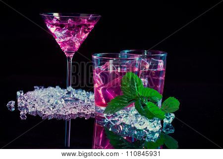 Wine Glass And Two Glasses With Pink Martinis, Fine Fragments Of Ice, Fresh Mint On A Dark Mirror Ba