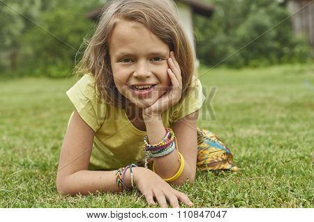 Nice ten year-old girl lying on the lawn with friendship bracelets on her wrists.