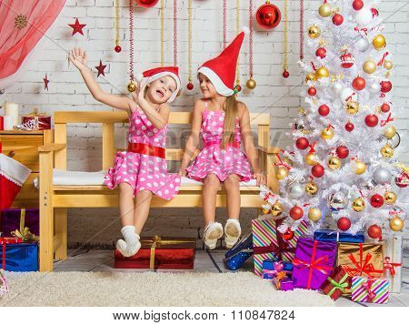 Two Funny Girls Fool Around Sitting On A Bench In A Christmas Setting