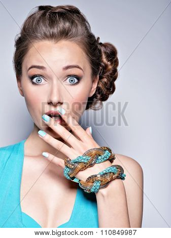 Young beautiful woman with jewelry. Girl Fashion  in blue dress wearing bijouterie. Attractive model with blue nails.