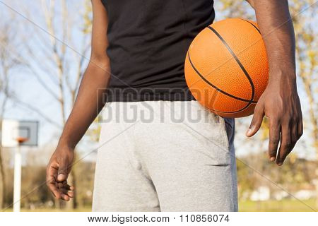 Closeup of street basket player standing with a basketball at the court