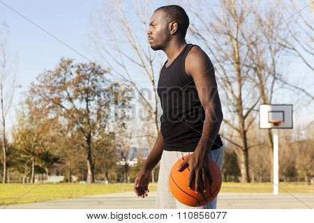Street basket player standing with a basketball at the court