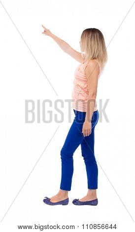 back view of pointing walking  woman. going girl pointing.  backside view of person.  Rear view people collection.  Girl in blue trousers leaves left looking at something in the sky.