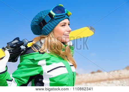 Portrait of beautiful skier woman over blue sky background, enjoying active winter sport, spending Christmas holidays in Alps, Europe