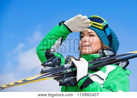 Skier instructor portrait, beautiful woman looking away, having fun in winter mountains, enjoying active vacation on ski resort in Alps