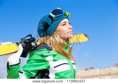 Portrait of beautiful gorgeous skier woman, wearing sportive clothes and holding in hands ski, active wintertime vacation