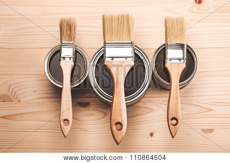 Paint brushes on three cans