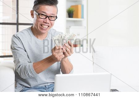 Portrait of 50s mature Asian man using internet computer and counting cash at home, earning money from his successful online business. Working from home concept.