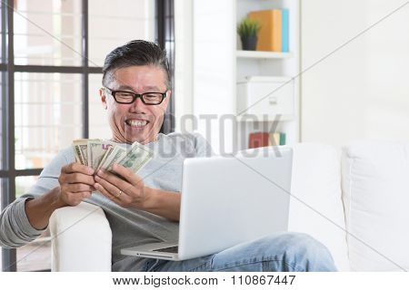 Portrait of happy 50s mature Asian man using internet computer and counting cash at home, earning money from his successful online business. Working from home concept.