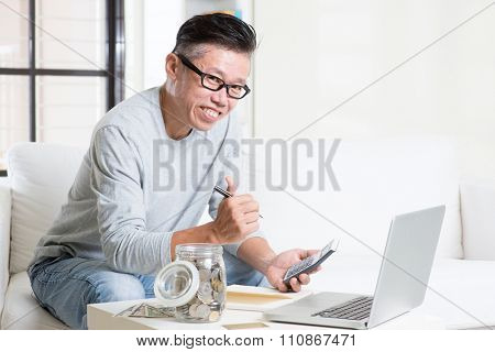 Mature 50s Asian man giving thumb up while counting on money using calculator and laptop computer. Saving, retirement, retirees financial planning concept.