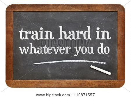Train hard in whatever you do - advice in white chalk on a vintage slate blackboard