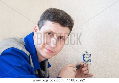 The Electrician Installs An Electrical Outlet In The Apartment.