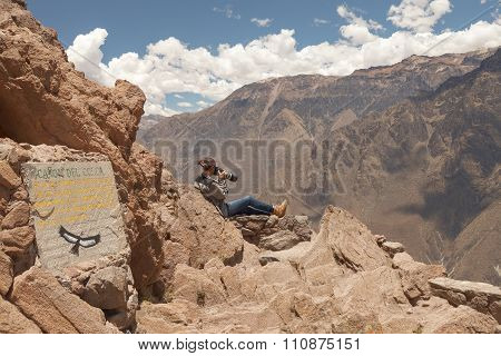 Young Woman Photographing Condors In Colca, Arequipa, Peru