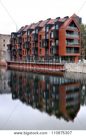 A modern multi-storey residential building, reflected in water