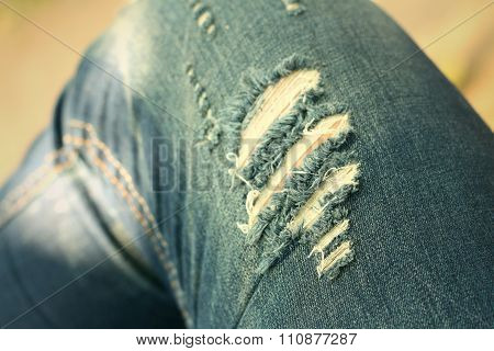 Torn  Jeans Of Men Seat At The Park