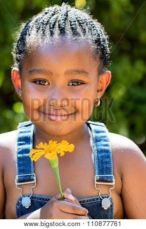Cute African Girl Holding Orange Flower Outdoors.