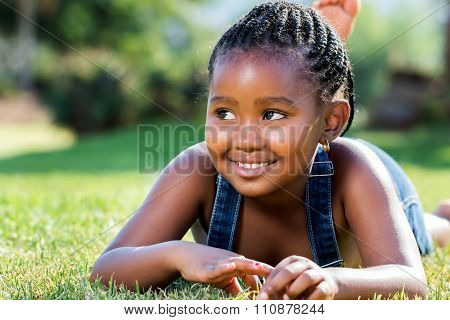 Cute African Girl Laying On Green Grass.