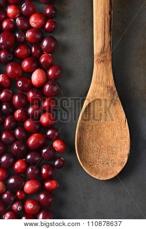 High angle view of fresh whole cranberries and a wooden spoon on a metal baking sheet. Vertical format.