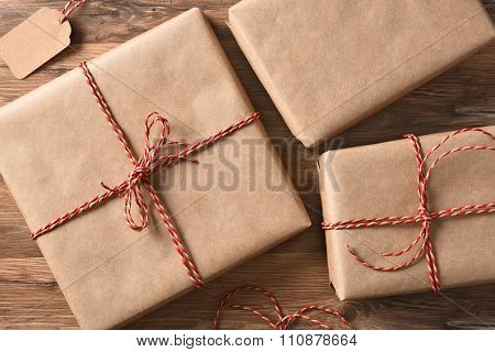 High angle view of three plain brown paper wrapped Christmas Presents on a rustic wood table.