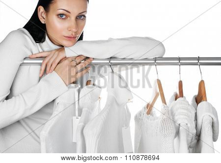 Portrait of young female with selection of winter clothes. Sale season concept.