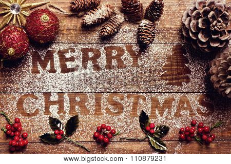 high-angle shot of a wooden table sprinkled with icing sugar where you can read the text merry christmas, and some pinecones and other christmas ornaments