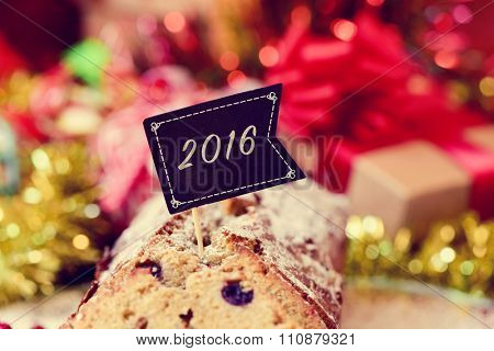 closeup of a fruitcake topped with a black flag with the number 2016, as the new year, on a table full of christmas gifts and ornaments