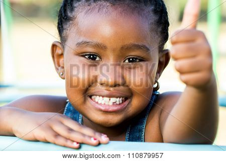 Face Shot Of African Girl Doing Thumbs Up Outdoors.