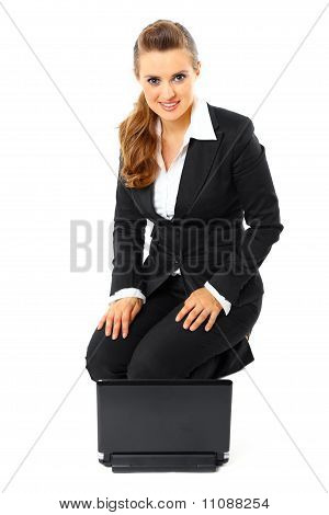 Smiling modern business woman sitting on floor with laptop isolated on white