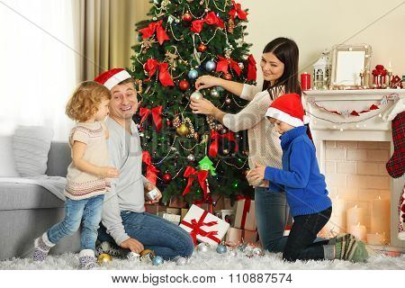 Happy family decorating Christmas tree in holiday living room