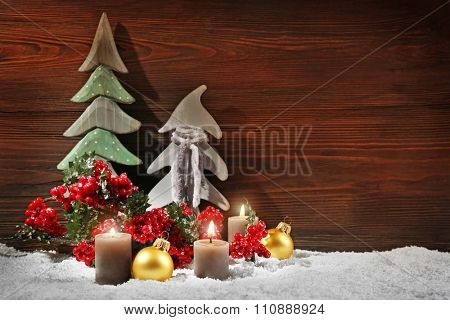 Fir trees, candles and balls with brunch of holly berries in a snow over wooden background, still life