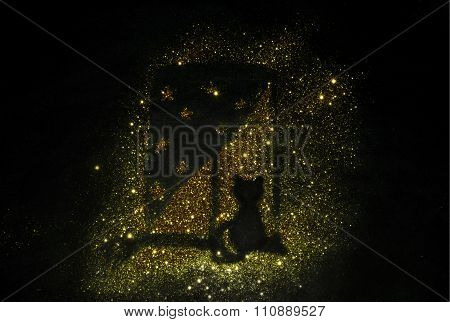 Silhouette of a cat on a window sill of golden glitter sparkle on black background