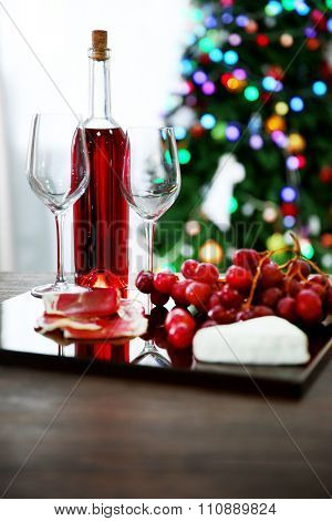 Pink wine bottle, two wineglasses, grape, slices of bacon and cheese on Christmas background