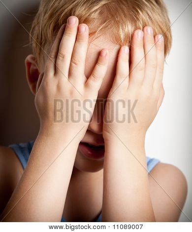 Portrait Of Sad Crying Child Covers His Face With Hands