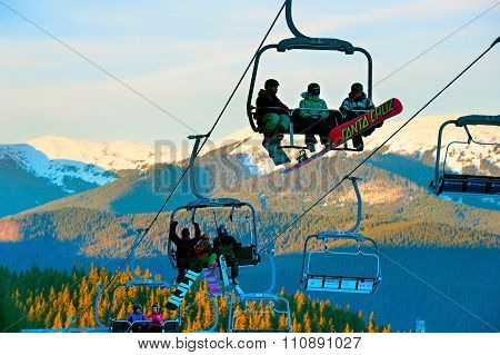 Skiers On Ski Lift At Sunset