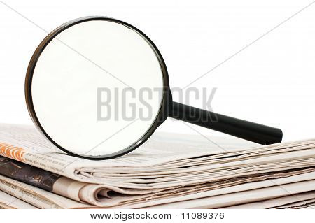 Magnify Glass Over A Stack Of Newspaper
