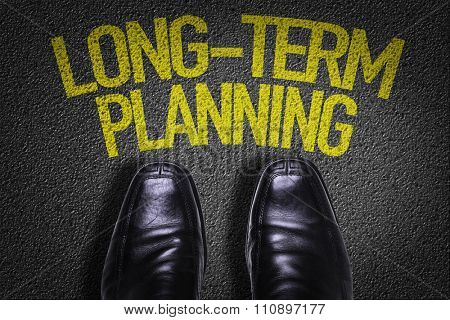 Top View of Business Shoes on the floor with the text: Long-Term Planning