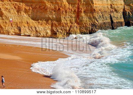 Tourist walking on Benagil Beach on the Algarve coast