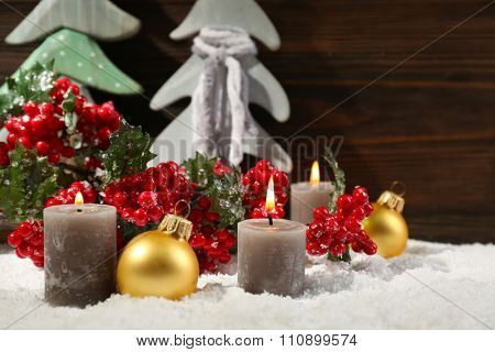 Fir trees, candles and balls with brunch of holly berries in a snow over wooden background, close up
