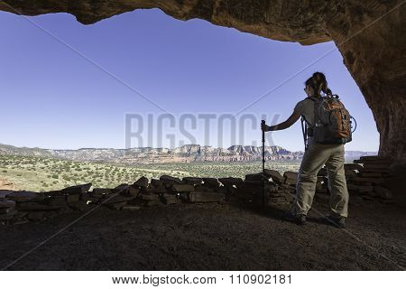 Woman Exploring Cave While Hiking