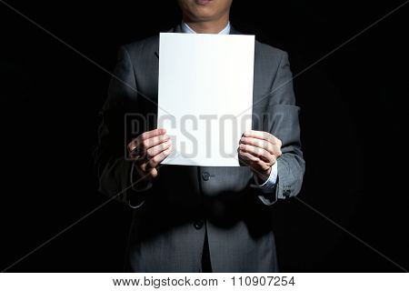 A handsome businessman with a goatee beard shows paper
