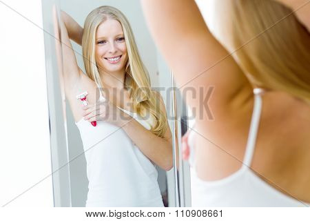 Beautiful Young Woman Shaving Her Armpit In Underwear.