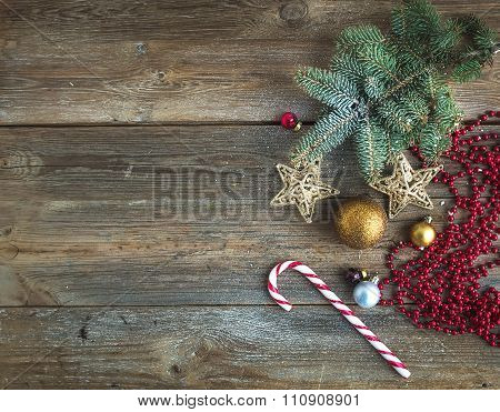 Christmas or New Year rustic wooden background with toy decorations, candy cane and fur tree branch,